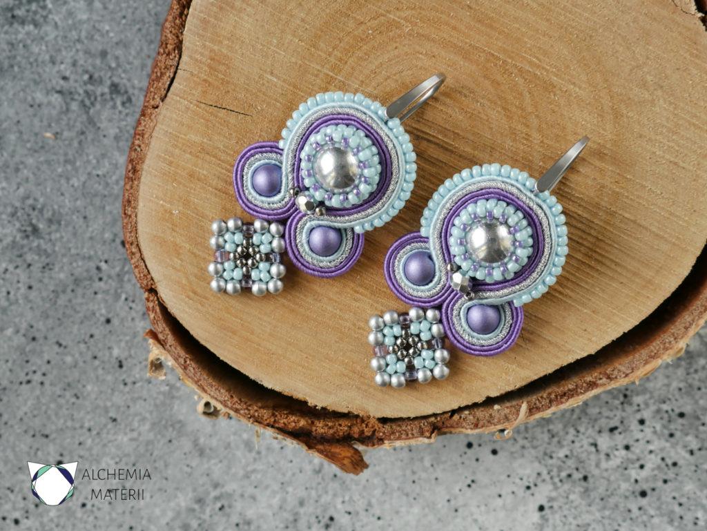 Kolczyki wykonane w technice haftu sutasz. W pastelowych barwach lawendowego fioletu , jasno błękitnego nieba oraz srebra.