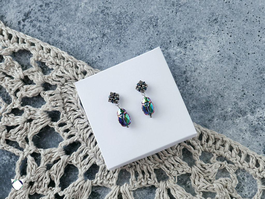 Kolczyki z kryształami Swarovskiego w kształcie żuka z akcentem koralikowym w metalicznych odcieniach zieleni i fioletu. Zawieszone na metalowych sztyftach ze stali chirurgicznej.