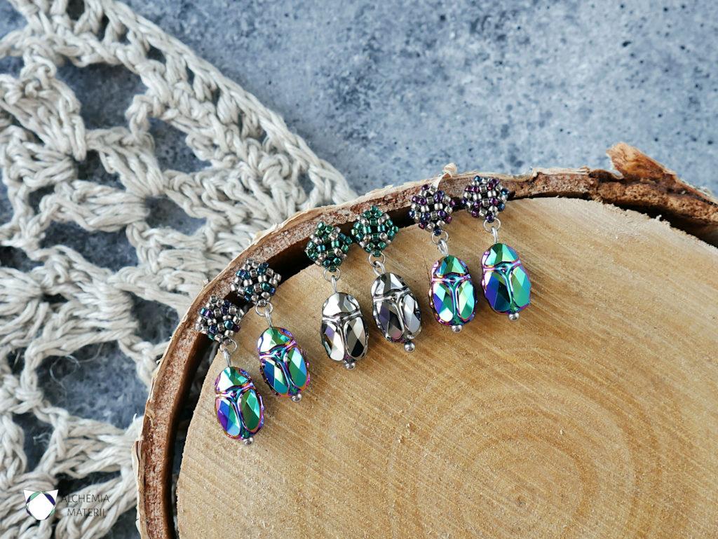 Kolczyki z kryształami Swarovskiego w kształcie żuka z akcentem koralikowym w metalicznych odcieniach stali ,zieleni i fioletu. Zawieszone na metalowych sztyftach ze stali chirurgicznej.
