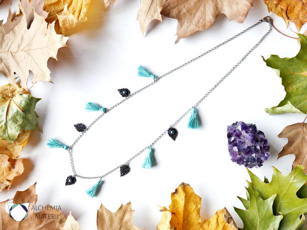 Naszyjnik z zawieszkami w kształcie liści i chwostami.