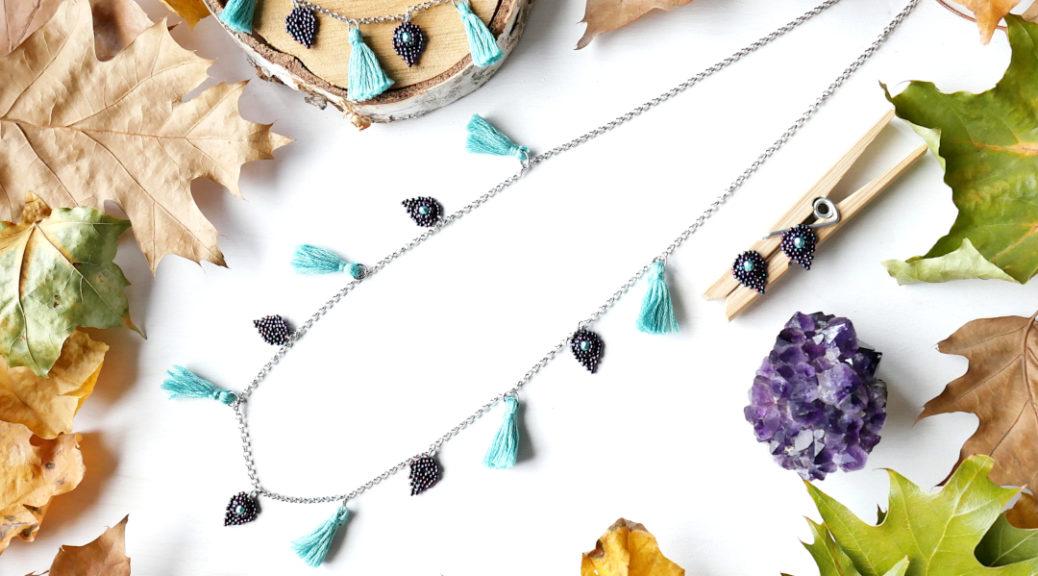 Komplet biżuterii z zawieszkami w kształcie liści i chwostami.